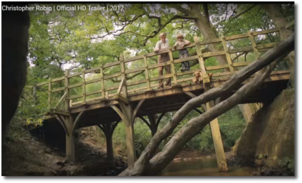 Christopher Robin plays Pooh-sticks with his dad from a wooden bridge