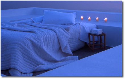 Rad outdoor bedroom on a bluff above the ocean with 4 candles under an infinite sky at sunset